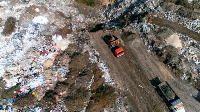 Aerial view of bulldozer and truck works on rubbish dump video