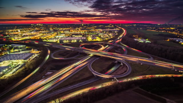 Aerial view of Busy Highway Intersection - Time Lapse Time lapse of a Highway Interchange (Autobahnkreuz) in Germany. Light-tails of the moving traffic. Moody sky at sunset. traffic time lapse stock videos & royalty-free footage