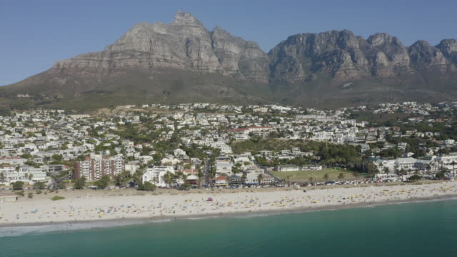 4k aerial view of camps bay beach with the 12 apostles mountains in the background, cape town,south africa - masso video stock e b–roll