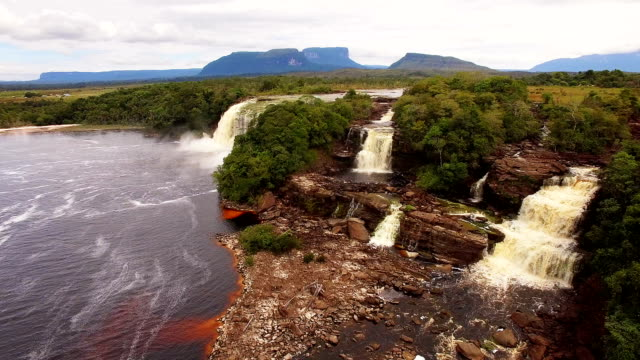 Aerial view of Canaima National Park Lagoon waterfalls. Canaima is a world known place for the beauty of nature and countless waterfalls. Canaima is visited for tourist all around the world. El Hacha waterfall at Canaima National Park lagoon, Canaima, Venezuela back to back stock videos & royalty-free footage