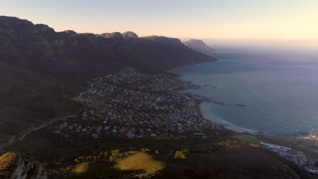 Aerial view of Cape Town coastline and mountains Beautiful aerial view of Camps bay beach from high up at sunrise, Cape Town, South Africa. cape peninsula stock videos & royalty-free footage