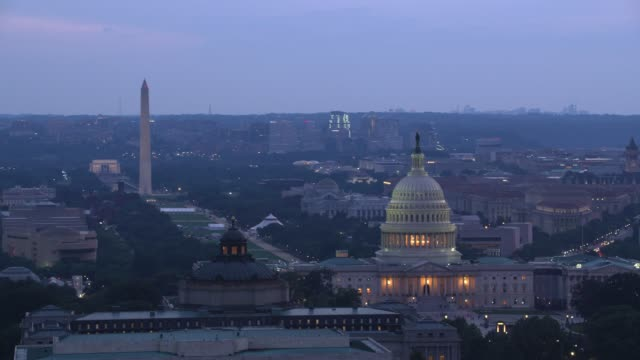 vidéos et rushes de vue aérienne du dôme du capitole et de la library of congress au crépuscule. - patriotisme