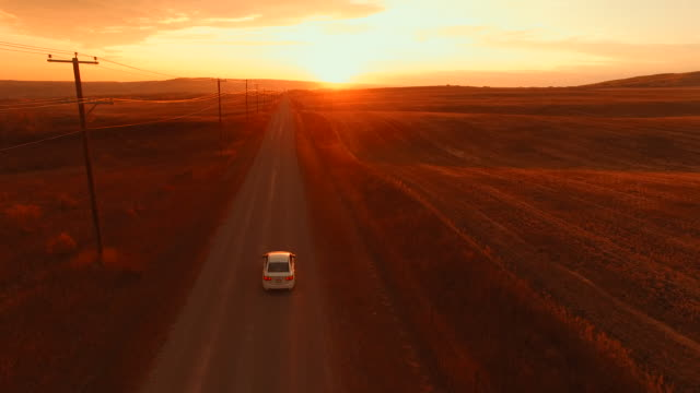 Aerial view of car driving down country road at sunset Birds eye view country road stock videos & royalty-free footage