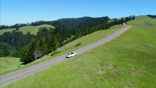 vídeos de stock, filmes e b-roll de vista aérea de carro estrada do país através de colinas rurais - veículo terrestre