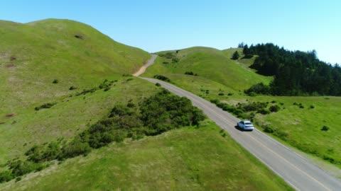 vista aerea dell'auto che guida lungo la strada di campagna attraverso dolci colline rurali - collina video stock e b–roll
