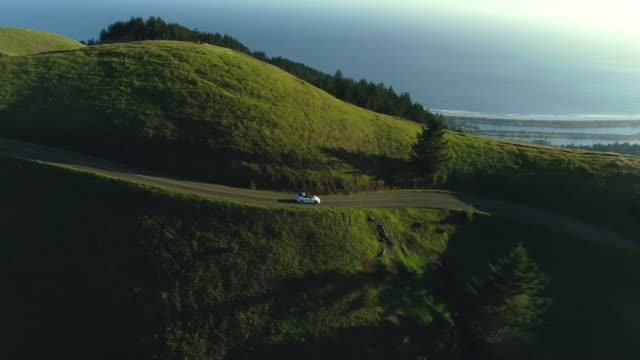 Aerial view of car driving down country road through rural rolling hills with ocean in background at sunset