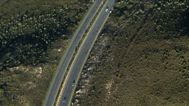 Aerial view of cars and trucks travelling along South African mountain pass, Du Toit's Kloof, Western Cape. Multi-lane road. Daytime, partly cloudy. video