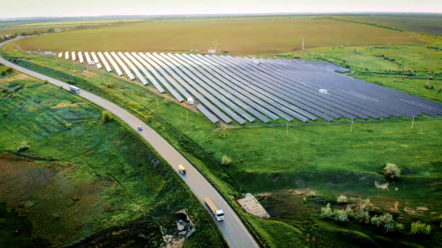 aerial view of cars and trucks with trailer drive on highway near solar power plant located in field - sustainability video stock e b–roll