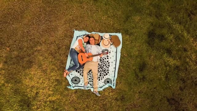 aerial view of caucasian couple lying down in the grass enjoying music with a guitar - picnic stock videos and b-roll footage