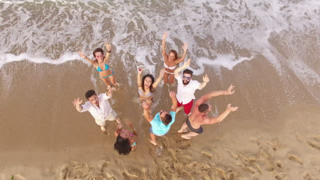 4K Aerial view of cheerful young people Group of young people having fun on beach - view from above. 4K brazil stock videos & royalty-free footage