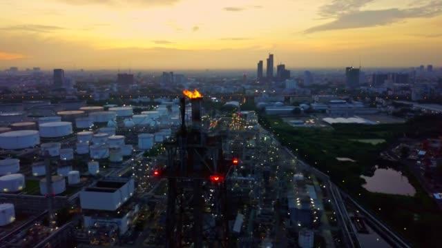 非常に熱いトーチを製油所や化学工場、都市の日の出貯蔵タンクの空撮 - 気体点の映像素材/bロール
