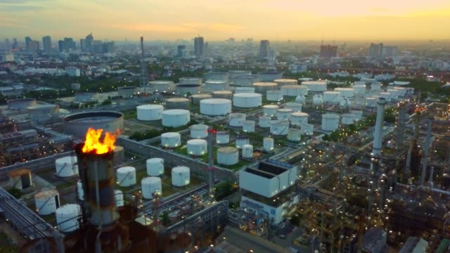aerial view of chemical or refinery plant with burning torch, storage tank at sunrise in the city - ископаемое топливо стоковые видео и кадры b-roll