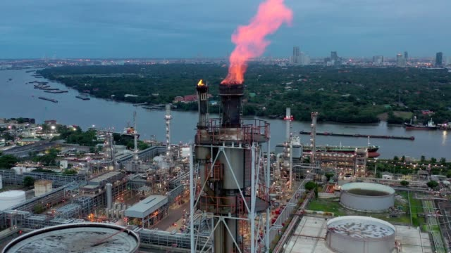 aerial view of chemical, refinery, power plant with burning torch, storage tank at sunrise near mountain and sea - ископаемое топливо стоковые видео и кадры b-roll