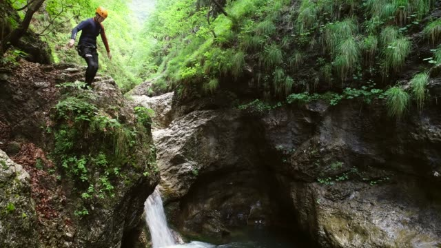 Aerial view of child jumping into the water in Soca river, Slovenia
