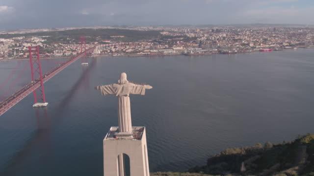vídeos de stock e filmes b-roll de aerial view of christ the king statue and tagus river - ponte 25 de abril