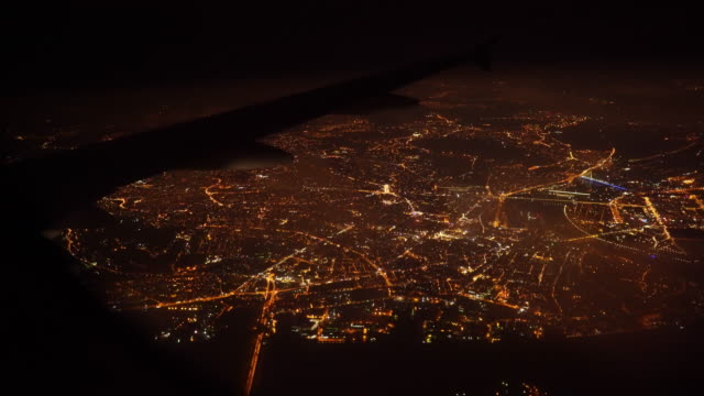 Aerial view of city at night when airplane flying on sky - Stock video