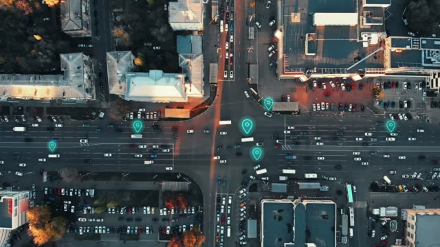 Aerial view of city intersection with many cars and GPS navigation system symbols. Autonomous driverless vehicles in city traffic. Future transportation concept video