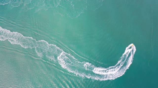 Aerial view of clear ocean and jet boat