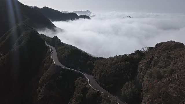 aerial view of clouds running over mountain road in anaga mountain range, tenerife, canary islands, spain. - passo montano video stock e b–roll