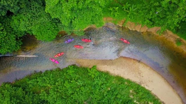カヤックのカラフルの空撮は、セーリングやタイの南の風光明媚な川に沿ってラフティング - エクストリームスポーツ点の映像素材/bロール