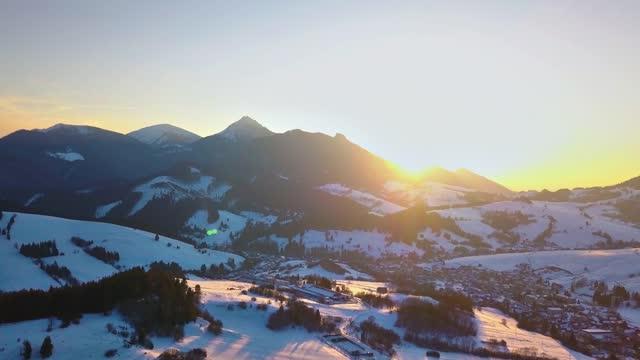 luftaufnahme des bunten wintersonnenuntergangs über der ländlichen landschaft in verschneiter alpiner naturlandschaft - slowakei stock-videos und b-roll-filmmaterial