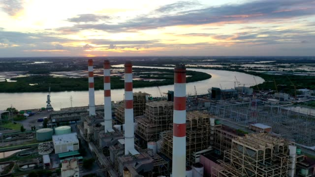 Aerial view of combined cycle power plant and Thermal powerplant with plume or steam at cooling tower at sunset