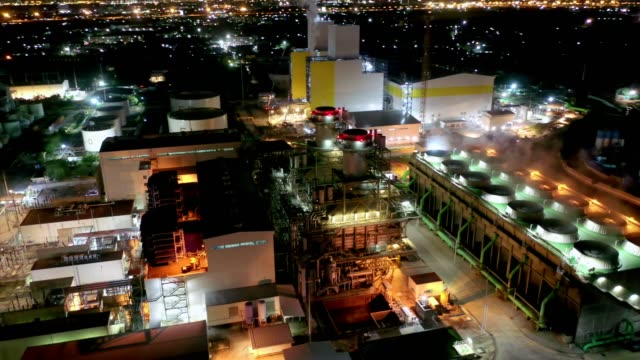 Aerial view of combined cycle power plant or fuel gas powerplant with cooling tower and plume or steam at cooling tower or steam at night