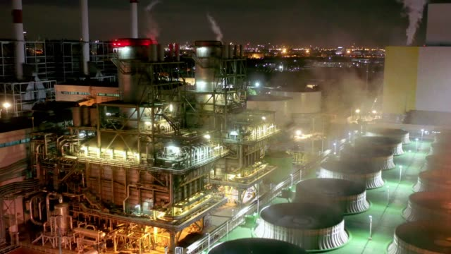 aerial view of combined cycle power plant or fuel gas powerplant with cooling tower and plume or steam at cooling tower or steam at night - centrale elettrica video stock e b–roll
