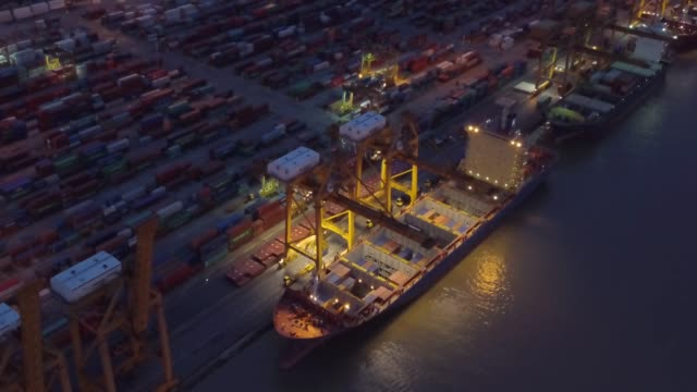 vídeos de stock e filmes b-roll de aerial view of container ship in the harbor at night shot. cloudy sky. - drone shipyard night