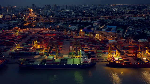 vídeos de stock e filmes b-roll de aerial view of container ship in the harbor at night - drone shipyard night