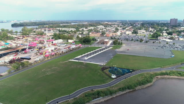 vídeos de stock e filmes b-roll de aerial view of cooper's point park and industrial docks with cranes on the shore of delaware river in camden, new jersey. drone video with the panoramic-rotating camera motion. - frente ao mar