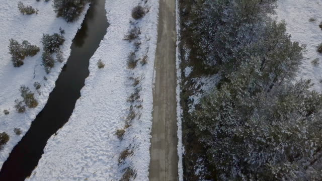 aerial view of country road and stream in the snow - rivulet 4k stock videos and b-roll footage