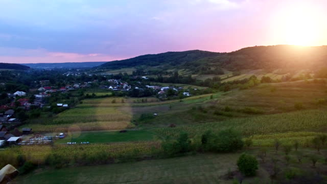 Aerial view of countryside village and crops, sunset video