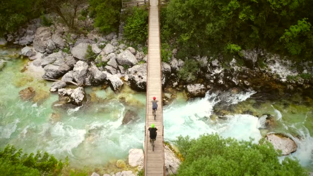Aerial view of couple crossing a wooden bridge on bicycles at the Soca River. Aerial view of couple crossing a wooden bridge on bicycles at the Soca River, Slovenia. suspension bridge stock videos & royalty-free footage