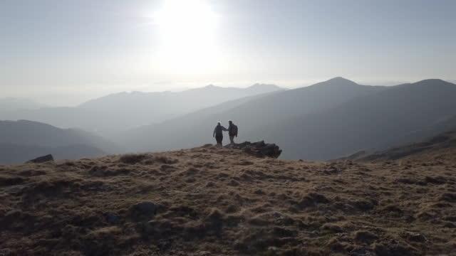 マウンテン トップ見て日没のカップルの空中写真 - バックパッカー点の映像素材/bロール