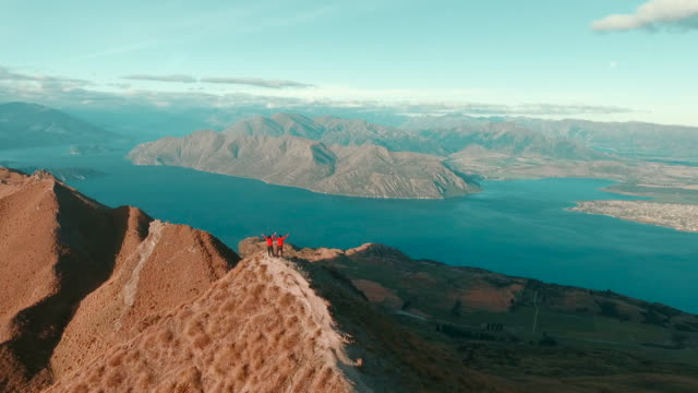 Aerial view of couple on mountain top watching viewpoint