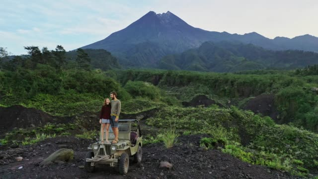 Aerial view of couple standing   old fashioned SUV on the background of Merapi volcano