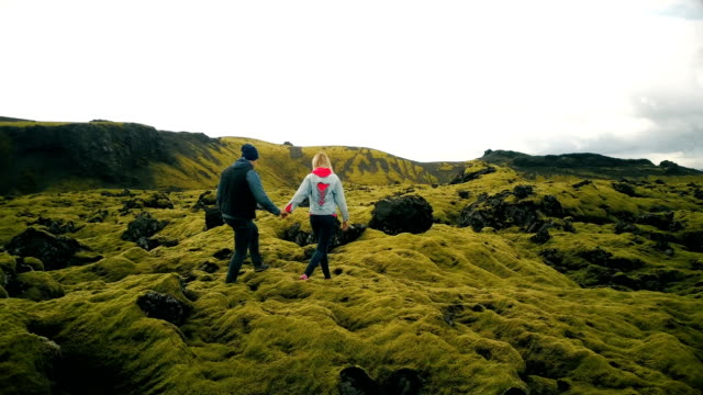 Aerial view of couple walking through the lava fields in iceland. Man and woman sit on the rock, enjoying the landscape video