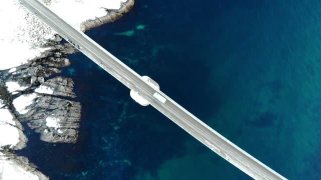 vídeos de stock e filmes b-roll de aerial view of cross island bridge with arctic coastline - noruega