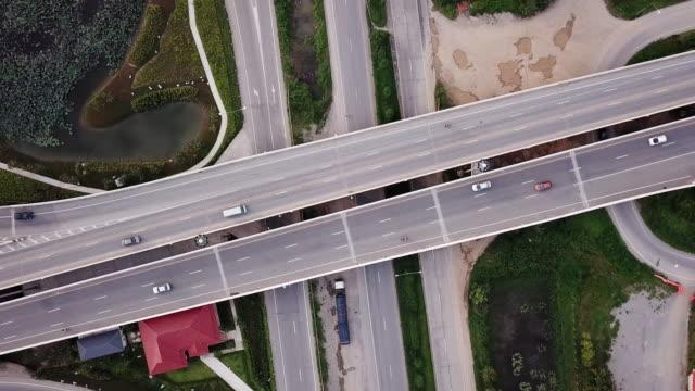 stockvideo's en b-roll-footage met luchtfoto uitzicht van kruispunt met stadsverkeer op snelweg, transport concept - dwarsweg