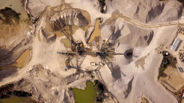 Aerial view of crushed stone quarry machine Descent over crushed stone quarry machine. construction vehicle stock videos & royalty-free footage