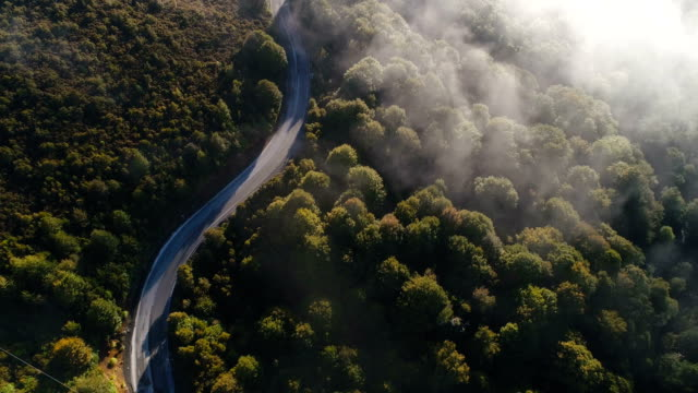 aerial view of curved road and low flying clouds passing. - время дня стоковые видео и кадры b-roll