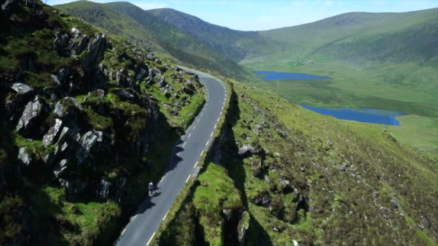 Aerial view of cyclist riding bicycle on majestic mountain road video