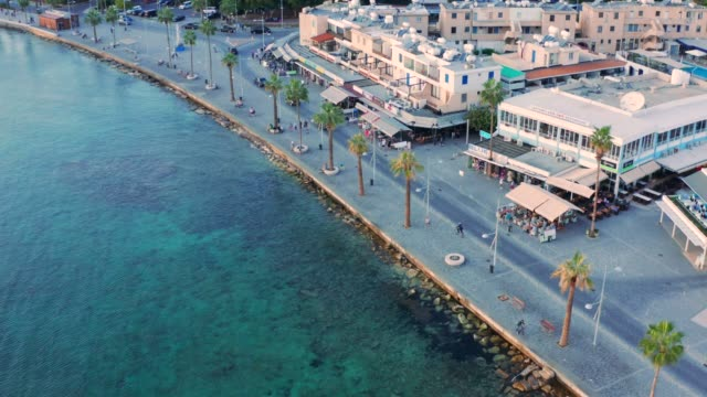 Aerial view of Cyprus resort Paphos promenade with cafes, hotel, beautiful sea and walking people. Drone footage of old famous mediterranean city for beach rest video