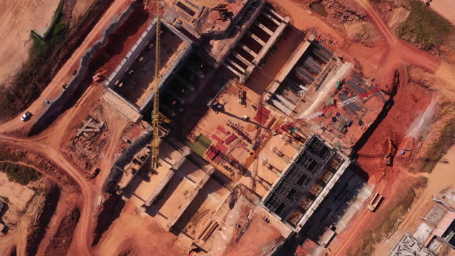 Aerial view of dam building in the process of construction, Construction Projects Using Cranes.World at work drone view concept.