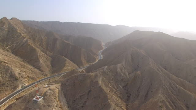 aerial view of desert valley in muscat bay region, road in desert surrounded by mountains, oman, sultanate on arabian peninsula, 4k uhd - oman filmów i materiałów b-roll
