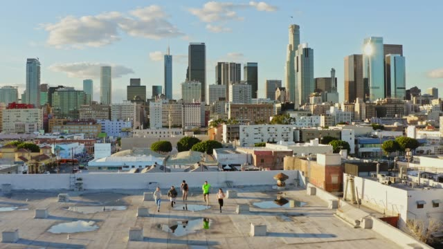 vídeos de stock e filmes b-roll de aerial view of diverse people running at a rooftop in downtown los angeles - young woman running city