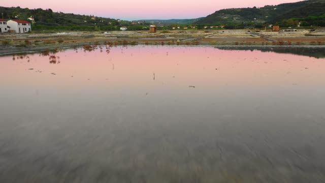 Aerial view of drone flying low with nice sunset reflection vibrant colors over the small salt pans where salt from see water is produced in Slovenia, Secovlje Aerial view of drone flying low with nice sunset reflection vibrant colors over the small salt pans where salt from see water is produced in Slovenia, Secovlje salt flat stock videos & royalty-free footage