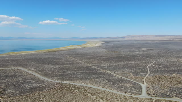 Aerial view of dusty dry desert land with Mono Lake on the background, Mono County