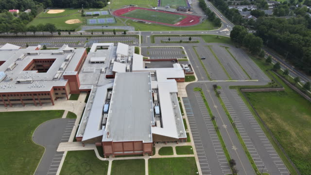 Aerial view of empty in school during coronavirus Covid-19 pandemic of locked closed empty stadium with basketball field and training ground in park